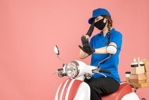 Vista frontale della ragazza stanca del corriere che indossa maschera medica e guanti seduti su uno scooter che consegna ordini su sfondo color pesca pastello