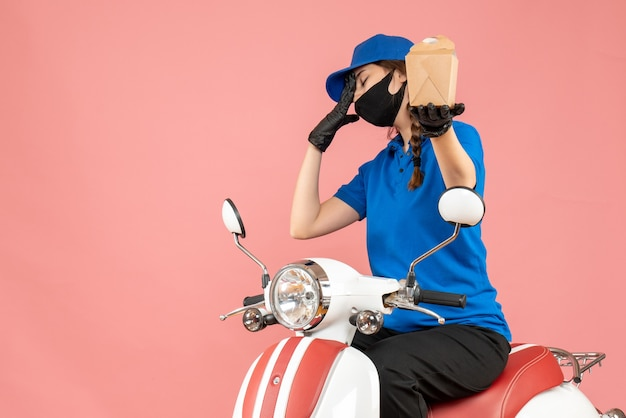 Vista frontale del fattorino stanco che indossa maschera medica e guanti seduto su uno scooter che consegna ordini su sfondo color pesca pastello