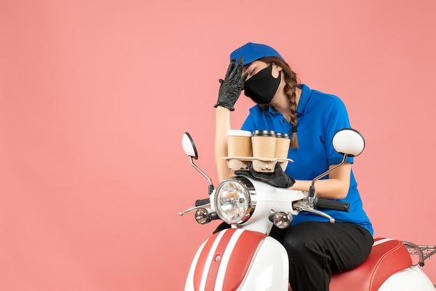 Vista frontale della donna stanca delle consegne che indossa maschera medica e guanti seduti su uno scooter che tiene ordini su sfondo color pesca pastello