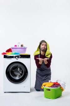 白い壁の上の膝の緑の洗濯かごの上に立っている正面図疲れた家政婦の男