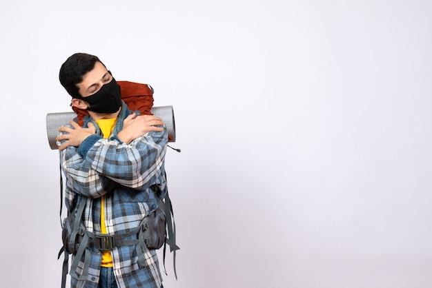 Viaggiatore maschio stanco vista frontale con zaino e maschera che si tiene