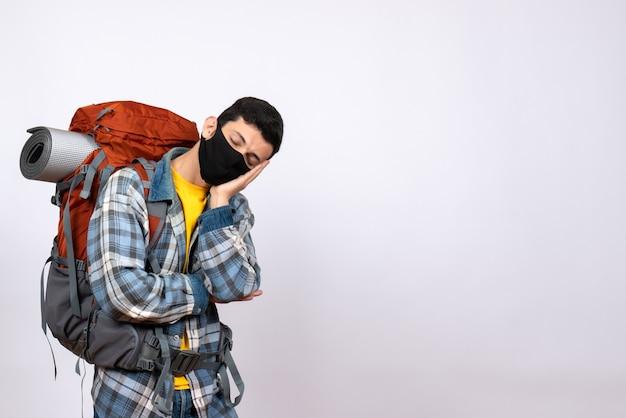 Viaggiatore maschio stanco vista frontale con zaino e maschera per dormire