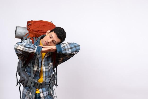 Вид спереди усталый путешественник со спящим рюкзаком