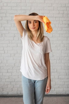 Front view of tired woman holding cleaning cloth