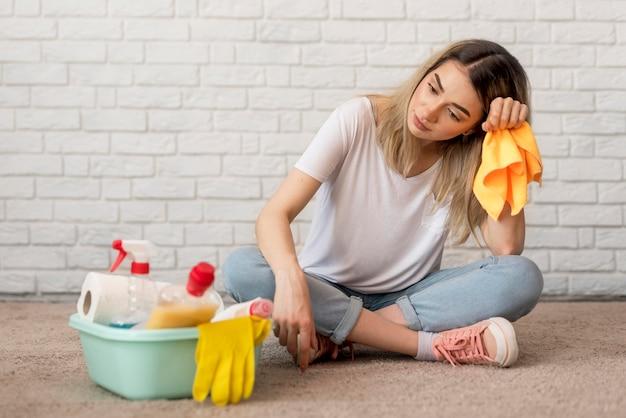 Vista frontale della donna stanca con prodotti per la pulizia e panno