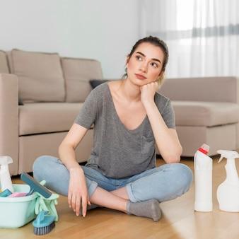 Vista frontale della donna stanca con prodotti per la pulizia