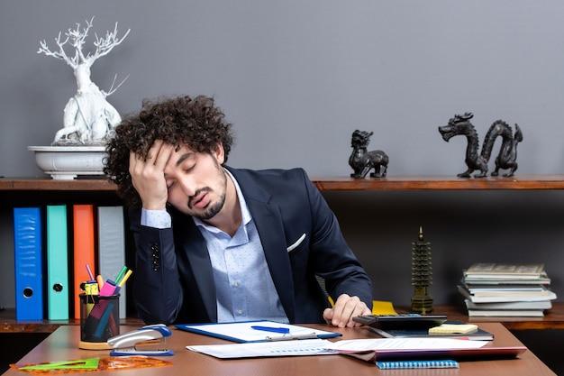 Vista frontale del giovane uomo d'affari stanco seduto alla scrivania in ufficio