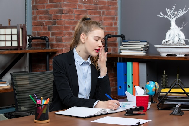 Vista frontale di una giovane donna stanca seduta a un tavolo e che scrive su un documento in ufficio