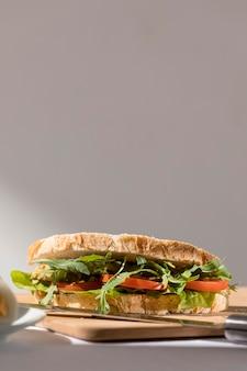 Vista frontale del panino tostato con pomodori, verdure e spazio di copia