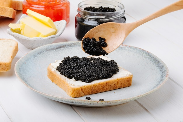 Front view toast with black caviar on a plate with a spoon and butter with a can of black and red caviar