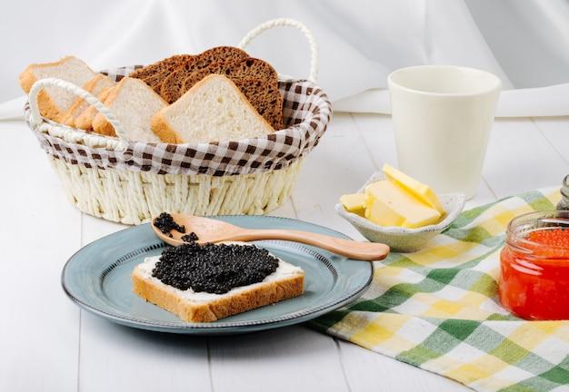 Вид спереди тост с черной икрой с ложкой на тарелке с красной икрой маслом и хлебом в корзине