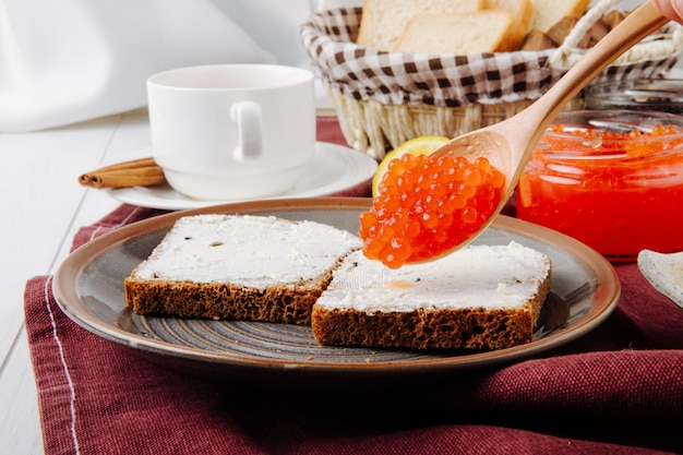 Вид спереди тосты с маслом и ложкой красной икры на тарелке с чашкой чая