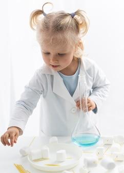 Vista frontale del bambino che impara a conoscere la scienza con marshmallow