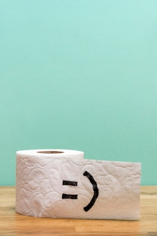 Front view of toilet paper roll with copy space and smiley face