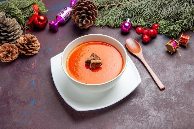 Томатный суп с нарезанным хлебом внутри на темном пространстве, вид спереди