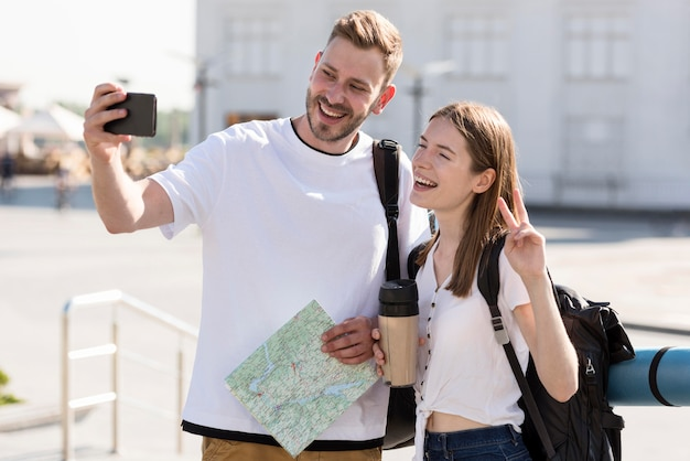 Front view of tourist couple outdoors with backpacks and map taking selfie