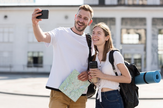 Front view of tourist couple outdoors with backpacks taking selfie