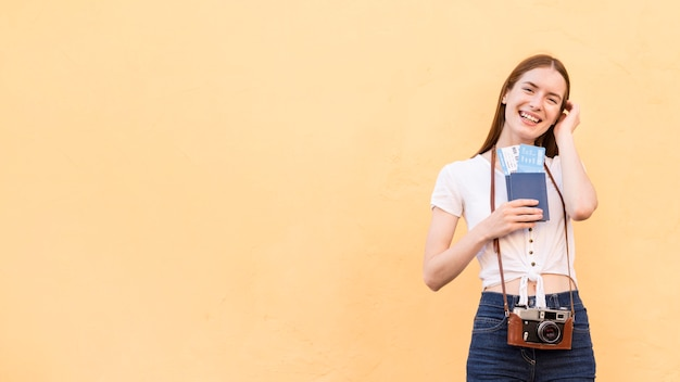 Front view of tourist woman with passport and camera
