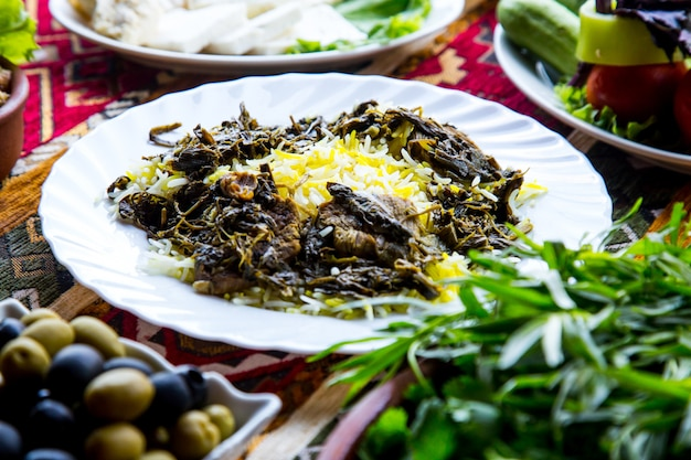 Front view traditional azerbaijani pilaf syabzi fried meat with greens and rice