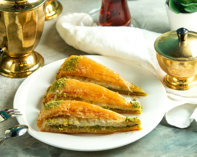 Front view traditional turkish sweetness turkish baklava with a glass of tea