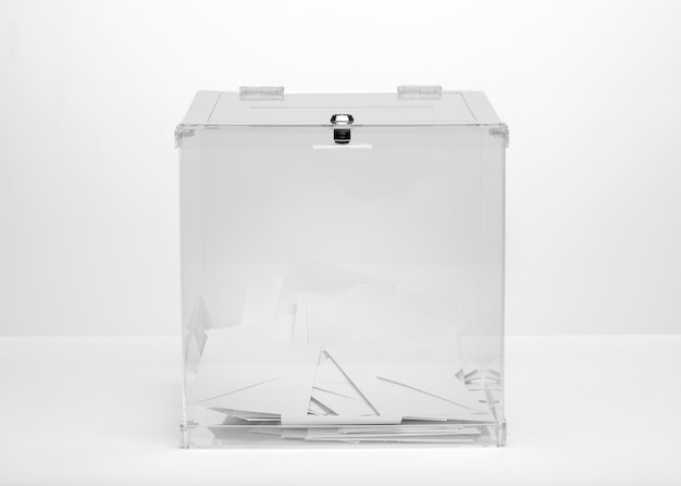 Front view transparent ballot box filled with vote bulletins
