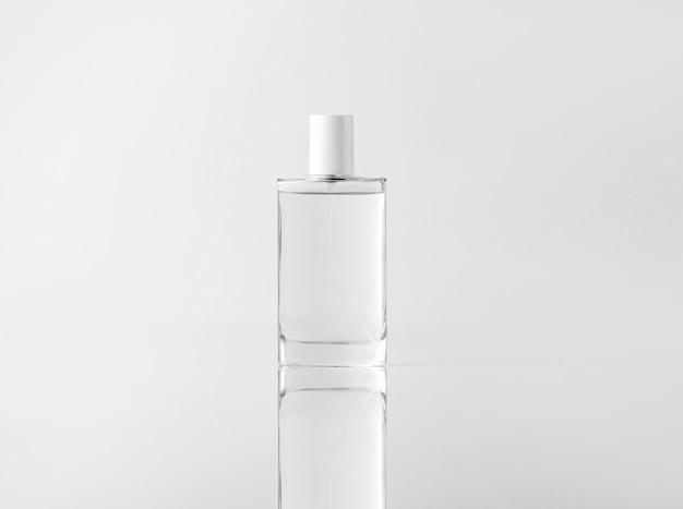 Una bottiglia trasparente vista frontale per le procedure di pulizia del viso sul muro bianco