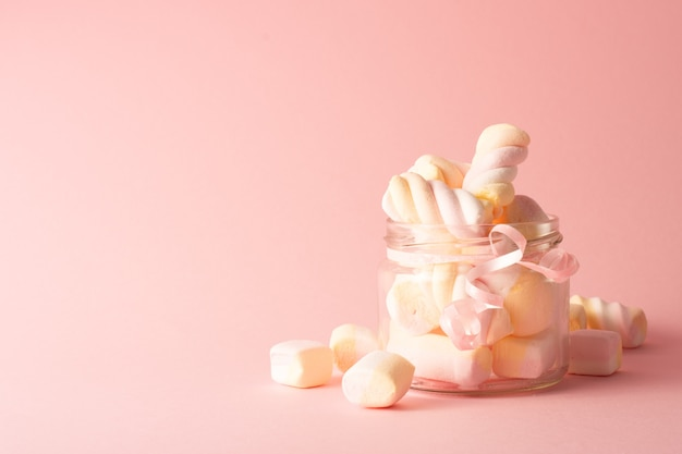 Front view of transparent jar with marshmallow and copy space
