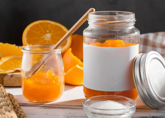 Vista frontale del barattolo trasparente con marmellata di arance