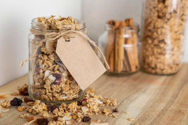 Front view of transparent jars with breakfast cereals and tag
