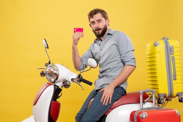 Vista frontale del concetto di viaggio con barbuto giovane uomo seduto sulla moto con valigie in possesso di carta di credito su di esso su giallo