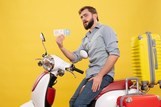 Vista frontale del concetto di viaggio con il giovane barbuto che si siede sulla motocicletta con le valigie che tengono il biglietto su di esso su colore giallo