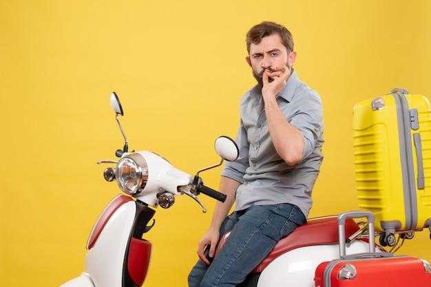 Vista frontale del concetto di viaggio con barbuto giovane uomo seduto sulla moto con le valigie che fa il gesto perfetto su di esso su giallo