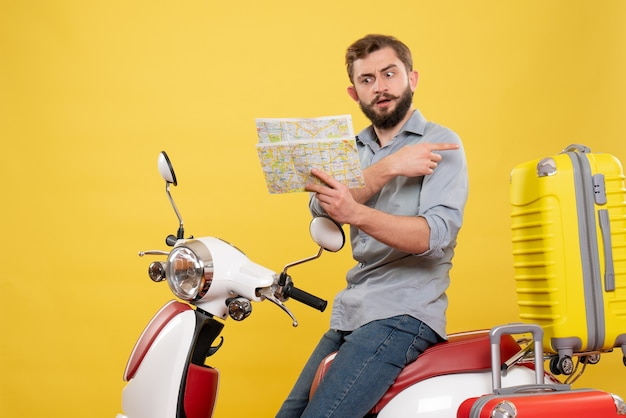 Front view of travel concept with confused young man sitting on motocycle with suitcases on it pointing back holding map on yellow