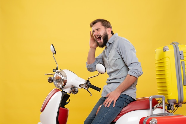 Front view of travel concept with emotional young man sitting on motocycle with suitcases on it shouting on yellow