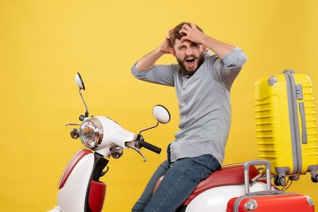 Vista frontale del concetto di viaggio con giovane nervoso esaurito che si siede sulla motocicletta con le valigie su di esso su colore giallo
