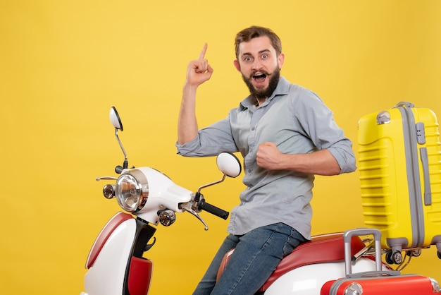 Vista frontale del concetto di viaggio con orgoglioso ambizioso giovane uomo seduto sulla moto con le valigie su di esso su giallo