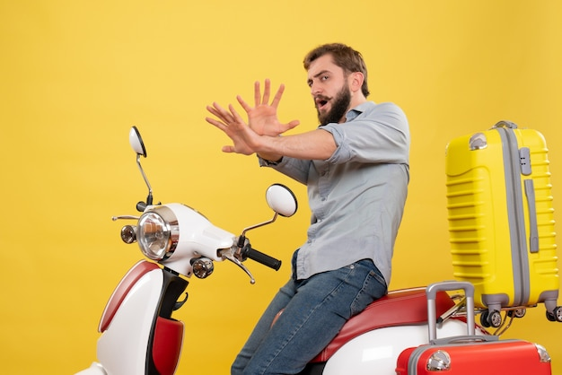 Vista frontale del concetto di viaggio con spaventato giovane uomo seduto sulla moto con le valigie su di esso su giallo