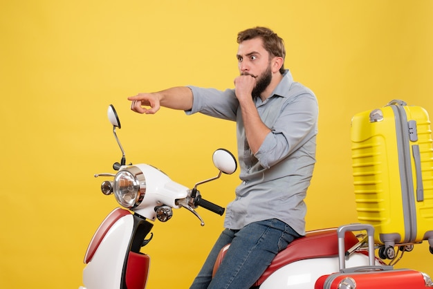 Vista frontale del concetto di viaggio con giovane scioccato seduto sulla motocicletta con le valigie rivolte in avanti su di esso su giallo