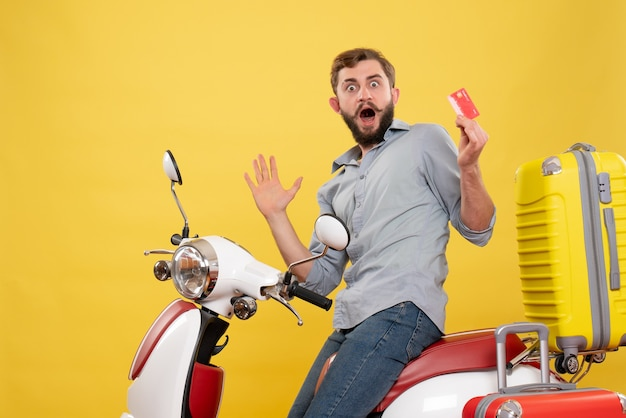 Front view of travel concept with surprised emotional young man sitting on motocycle with suitcases on it holding bank card on yellow