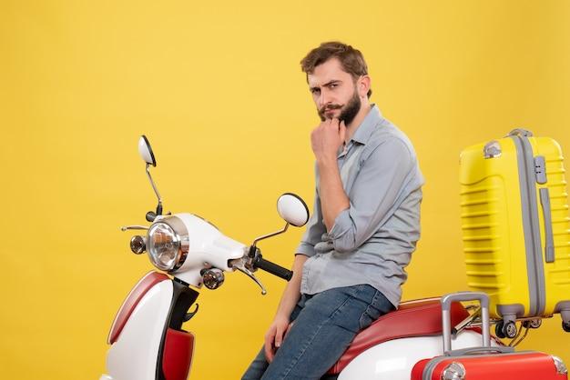 Vista frontale del concetto di viaggio con il giovane premuroso che si siede sulla motocicletta con le valigie su di esso su colore giallo