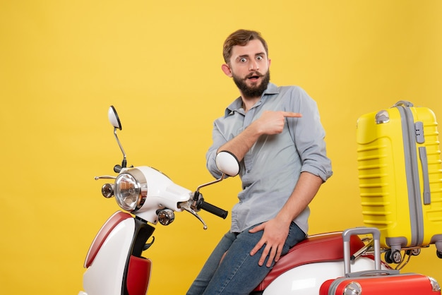 Front view of travel concept with wondering young man sitting on motocycle with suitcases pointing back on it on yellow