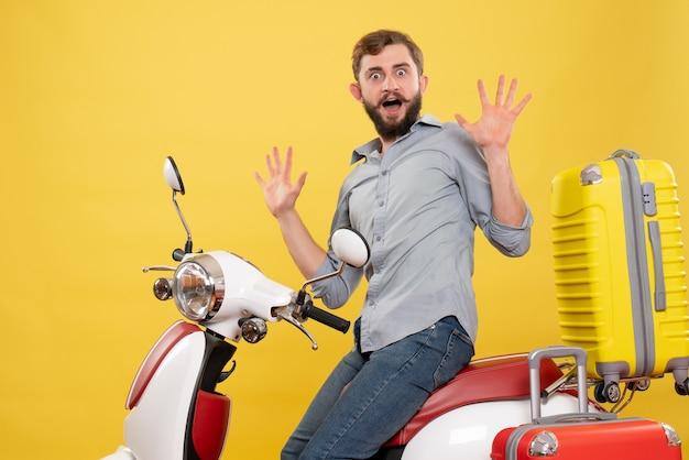 Vista frontale del concetto di viaggio con il giovane che si siede sulla motocicletta con le valigie che si sente nervoso su di esso su giallo