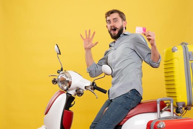 Vista frontale del concetto di viaggio con il giovane che si siede sulla motocicletta con le valigie che tengono la carta di credito che si sente nervoso su di esso su giallo