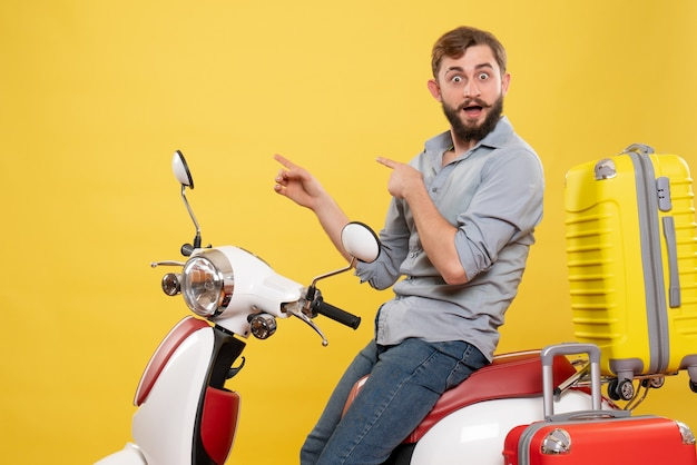 Front view of travel concept with young surprised bearded man sitting on motocycle pointing back on it on yellow