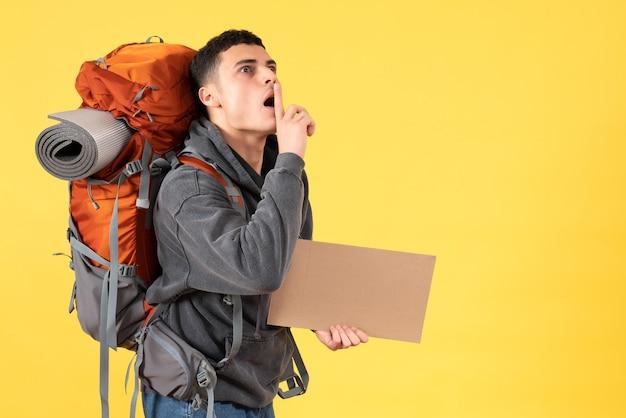 Человек-путешественник, вид спереди с рюкзаком, держащий картон, делая знак тишины