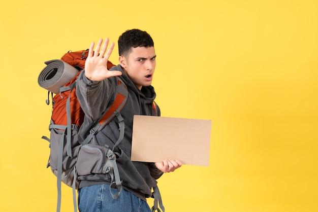 Человек-путешественник, вид спереди с рюкзаком, держащий картон, делая знак остановки