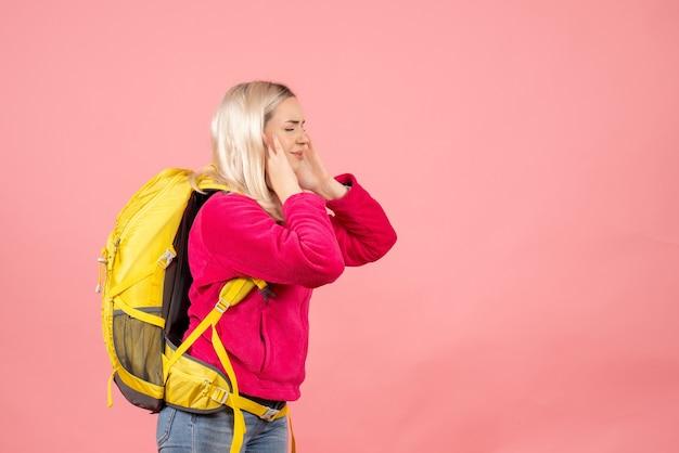 手で耳を閉じるバックパックと正面の旅行者の女性