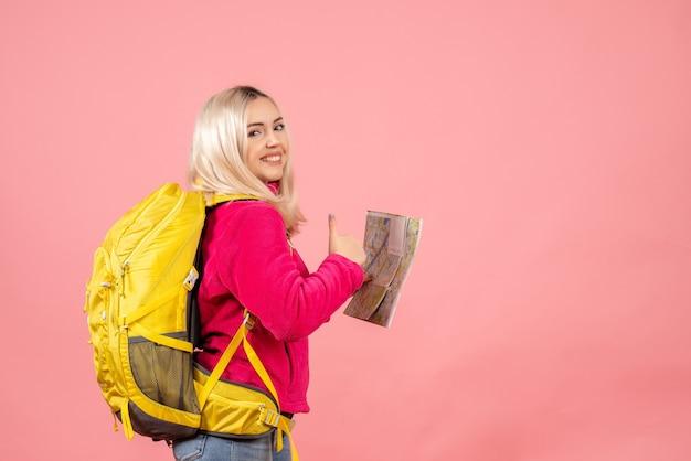 Женщина-путешественница вид спереди с рюкзаком показывает палец вверх, держа карту