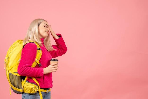 目を閉じてコーヒーカップを保持しているバックパックと正面の旅行者の女性