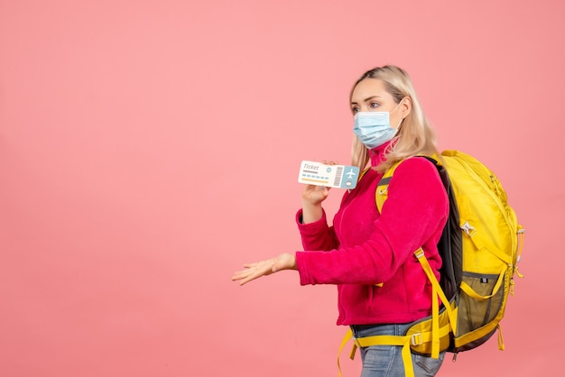 Женщина-путешественница с маской, держащая билет на розовой стене, вид спереди